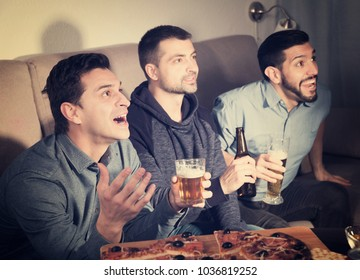 Exalted friends watching tv together at home, enjoying beer and pizza at home