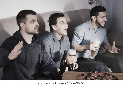Exalted male friends watching tv together at home, enjoying beer and pizza
