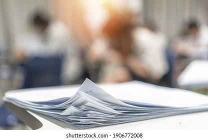 Prüfungsbogen-Stapel, unscharfer Bewerbungsunterlagen auf Büroarbeitstisch im Prüfungsraum oder Klassenzimmer mit unscharfem Unterrichtsunterricht Studierende, die eine Prüfung ablegen