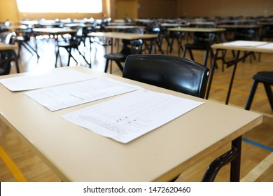 exam examination room or hall set up ready for students to sit test. multiple desks tables and chairs. Education, school, student life concept. test exam paper open