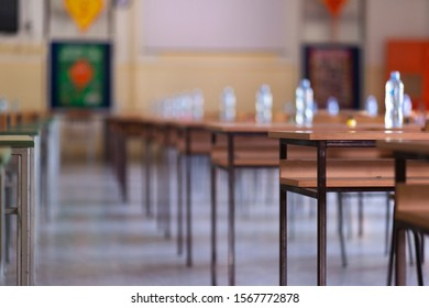 Exam examination room or hall set up ready for students to sit test. multiple desks tables and chairs. Education, school, student life concept.