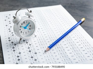 Exam form, pencil and alarm clock on table