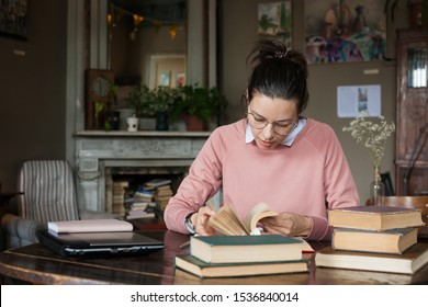 Exam preparation. Attractive brunette student girl in glasses and a pink sweater leaned over books, is engaged in an old library at the table, among stacks of books. Studying, preparing for tests,
