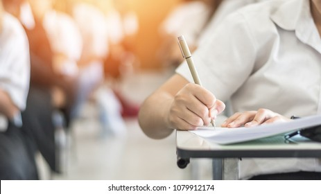 Exam with school student having educational admission test, thinking hard, writing answer in classroom for university education and world literacy day concept