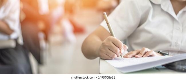 Examen à l'école avec un étudiant qui passe un examen d'admission scolaire en classe, réfléchit dur, écrit une réponse dans la classe universitaire, l'éducation et le concept de la journée mondiale de l'alphabétisation