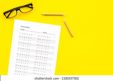 Exam sheet on yellow table top view copy space. Education concept. Exam problems. Broken pencil near exam sheet