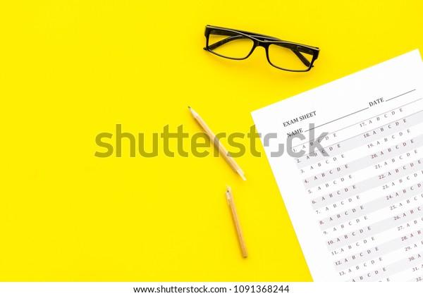 Exam sheet on yellow table top view copy space. Education concept. Exam problems. Broken pencil near exam sheet