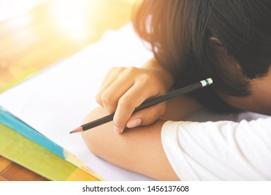 exam stress / education young female college in class taking notes and using a pencil sitting learning concept stressed student girl asian take the exam final  and sleeping on books