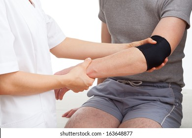 Examination of injured elbow of tennis player