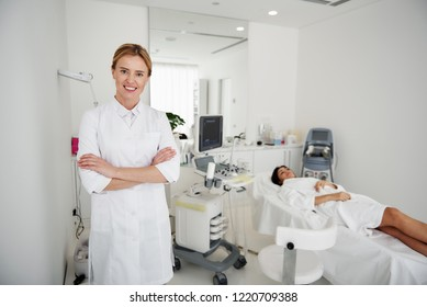 Examination is over. Portrait of beautician in white lab coat looking at camera and smiling. Brunette woman in bathrobe lying on daybed on blurred background