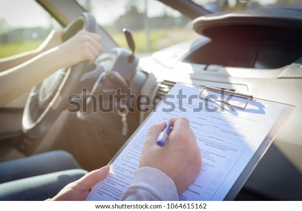 Examiner filling in driver's license road test form sitting with her student inside a car