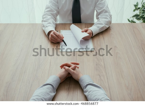 Examiner reading a resume during a job interview, employment and recruitment concept, point of view shot