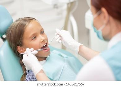Examining cute schoolgirl. Experienced child dentist wearing gloves examining cute schoolgirl
