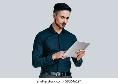 Examining his digital tablet. Serious young man in shirt working on his digital tablet while standing against grey background