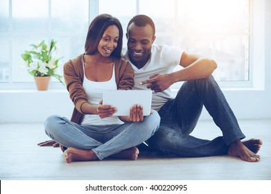 Examining their new tab. Beautiful young African couple using digital tablet while sitting together on the floor at their apartments
