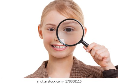 Examining you. Cheerful little girl in formalwear examining you with magnifying glass while standing isolated on white
