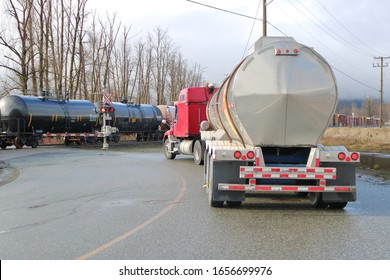 An example of the different types of transportation used to transport dangerous fuels as train rail cars shipping chlorine pass a waiting semi trailer with petroleum.