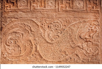 Example of indian artworks from near 7th century, mythical hero jumping out of the mouth of a giant sea monster. Ancient relief on ceiling of Hindu temple in Karnataka, India.