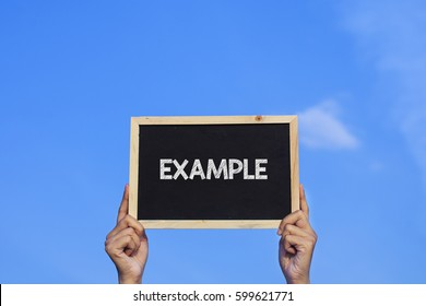 EXAMPLE/ Man holding small blackboard on blue sky background