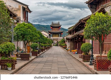 Example of Well Preserved Historic Main Street with Tower Gate and Mountains in Weishan, Yunnan Province, China. Pedestrian Street in Traditional Mountain Town in Southern China.