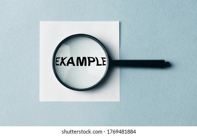 Example word inscription on paper note through magnifier. example concept. searching for example, explore examples