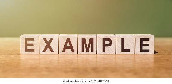 EXAMPLE word written on wooden blocks on wooden table. Concept for your design