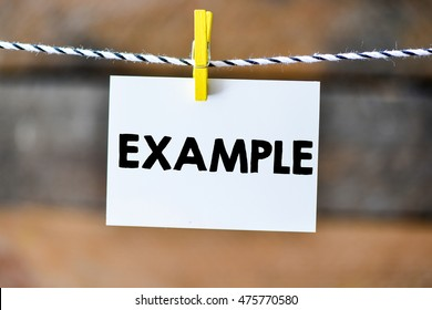Example.Example on paper hanging on the clothesline. On old wood background