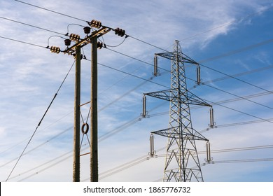 Examples of two overhead electricity pylons. Lattice steel pylon and a wooden pole pylon. Hertfordshire. UK