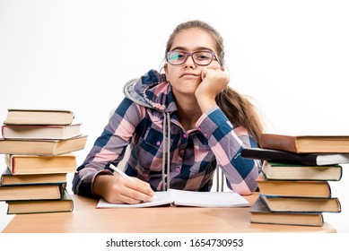 Exams at school. Girl with books. student is sitting at the table with books. Education. Tired of studying. Printed books, study at school. Library.