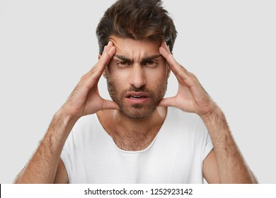 Exasparated unshaven man keeps hands on temples, has terrible headache, feels tired of constant work, has dark stubble, wears casual t shirt, isolated over white studio background. Close up shot.