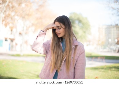 Exasperate female keeps hands on temples, feels strong headache, closes eyes with pain, need healthy sleep, being overworked, fatigue and tired. Blonde woman being ill, isolated outdoors