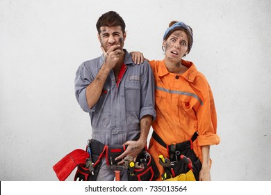 Exasperate service workers with unhappy expressions, want to have rest after hard work, stand together, realize that they should repair one more sewage, isolated over white studio background