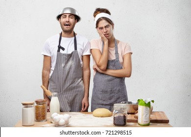 Exasperate tired female and male, prepare for grandious party, cook all day and night, have exhausted or fatigue expression, stand near table with dough for baking pie, going to cry in despair