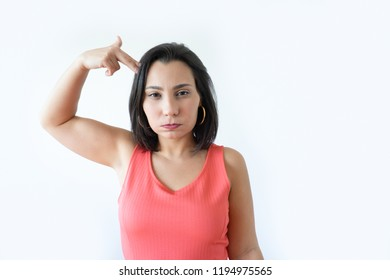 Exasperated attractive Caucasian woman showing suicide gesture with pursed lips. Pretty middle aged woman in pink dress staring at camera. Bored to death concept.