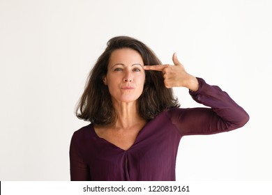 Exasperated Caucasian woman showing suicide gesture. Pretty middle aged woman looking at camera. Bored concept
