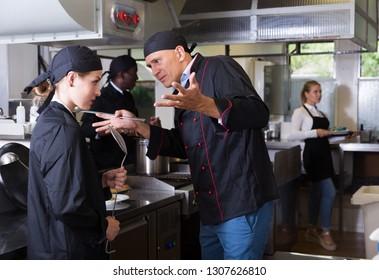 Exasperated head chef scolding upset female employee in kitchen of restaurant