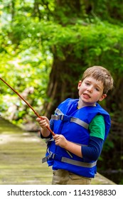 An exasperated little boy looks at the camera in frustration because his fishing pole is caught in a tree.  There is sweat dripping down the side of he is gritting his teeth.