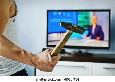 Exasperated the young man the bad news breaks the TV with a hammer. A psychopath beats TV. Disgruntled viewer. furious, enraged, frenzied, mad, infuriated man watches the news