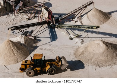Excavartor taking out the white gravel selected by sorter machinery in surface gravel quarry