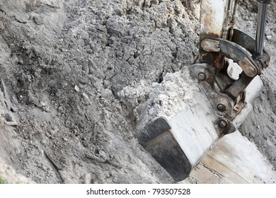 excavating earth-moving digger close up with hydraulic bucket and boom. digging a hole in sand
