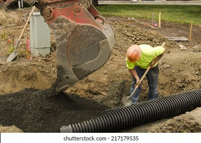 Excavation construction contractor installing a domestic black plastic sewer drain on a new commercial street filling with gravel