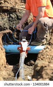 Excavation workers installing tracing wire on new water lines on a new commercial residential development