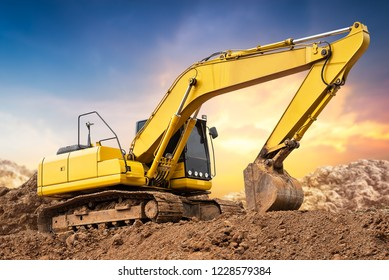 Excavator backhoe on the ground at construction site in sunset background