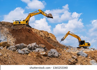 Excavator, Backhoe and rock crushing machine of mining under a blue sky with clouds