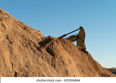 Excavator Behind a Mound of Dirt Against a Blue Sky