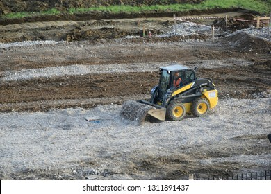 excavator bob cat working in a field for level the ground