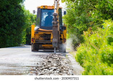Excavator breaking and drilling the concrete road for repairing. Large pneumatic hammer mounted on the hydraulic arm of a construction equipment. Construction Vehicles repairing road. drill jackhammer