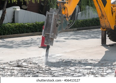 Excavator breaking and drilling the concrete road for repairing