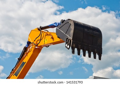 Excavator bucket against the sky