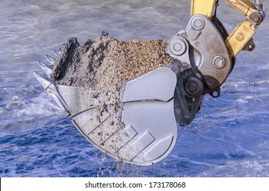 Excavator bucket dredging sand and gravel from the seafront